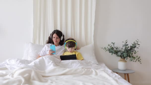 Mom and kid boy obsessed with gadgets spend morning in bed using smartphone and tablet in bedroom