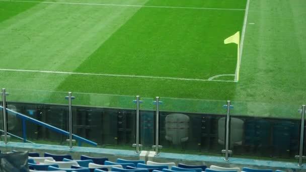 Žlutá rohová vlajka vlající ve větru na fotbalovém hřišti