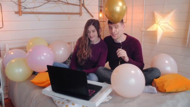 Young couple with balloons congratulates happy birthday by video call on laptop