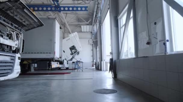 Pohled na opravárenský areál s bílými kamiony na čerpací stanici nákladních automobilů.