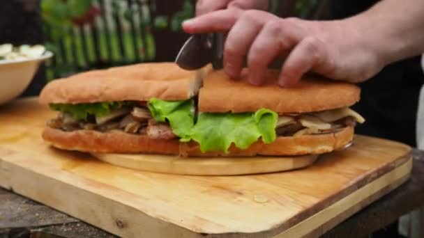 a man cuts a large Burger with salad and meat. mega sandwich with meat on the cut