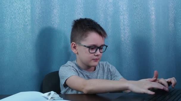 egy szemüveges fiú a számítógépen, aztán megfordul és felemeli a hüvelykujját. osztály