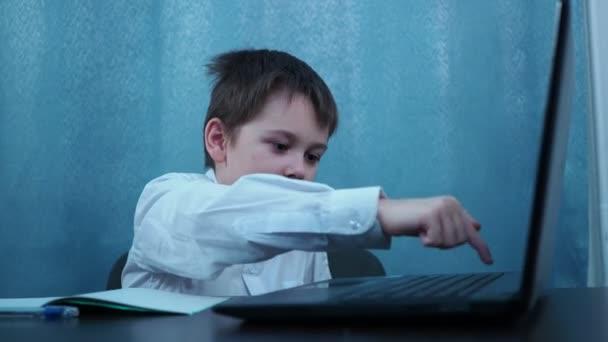 Egy pólós fiú gépel egy laptop kulcsain, ami egy asztalnál ül. A gyerekek játszanak tanulás helyett.