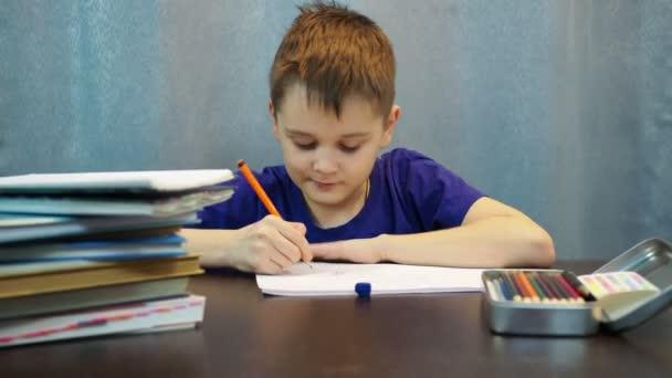 Egy pólós fiú rajzol papírra egy rajzot egy ceruzával az asztalnál. művészeti osztályok