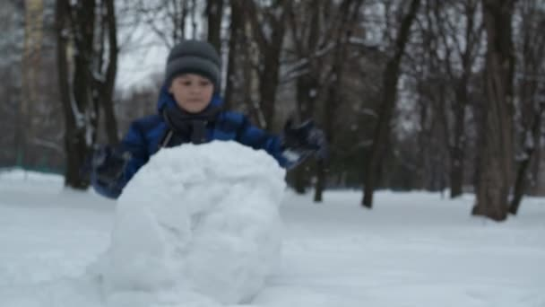 Weihnachtskurse. ein Junge in blauer Jacke modelliert aus Schnee