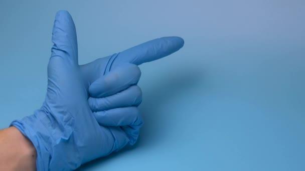 Eine Hand im Medizinhandschuh zählt bis fünf auf blauem Hintergrund. Arzthand.