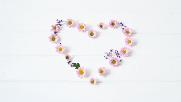 floral arrangement of pink chrysontema flowers in the shape of a heart on a white wooden background with place for text