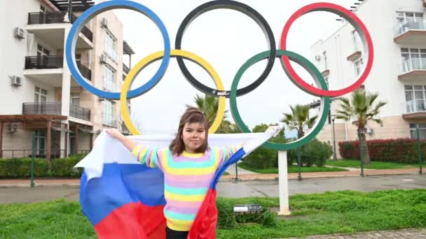 06,04,2021 Russia, Sochi one person little funny happynes girl stands with the flag of russia next to the Olympic rings the theme of the olympic games
