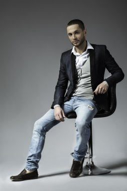 full length picture of a young business man sitting on a chair
