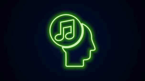 Ragyogó neon vonal Zenei megjegyzés az emberi fej ikon elszigetelt fekete háttérrel. 4K Videó mozgás grafikus animáció