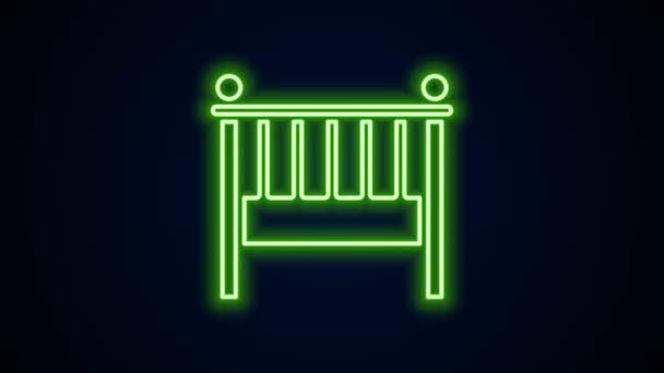 Világító neon vonal Babaágy bölcsőágy ikon elszigetelt fekete háttér. 4K Videó mozgás grafikus animáció