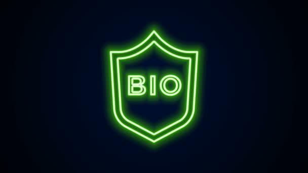 Ragyogó neon vonal Pajzs bio zöld egészséges élelmiszer ikon elszigetelt fekete alapon. Organikus termék. Egészséges ételmatrica. 4K Videó mozgás grafikus animáció