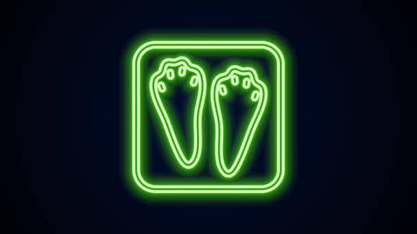 Leuchtende Leuchtschrift Kaninchen und Hasenpfote Fußabdruck Symbol isoliert auf schwarzem Hintergrund. 4K Video Motion Grafik Animation