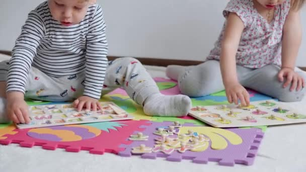 Childhood, family, insulation concept - group two small children collect soft puzzles fruits on board sitting on floor. kids Brother and sister playing educational games for motor skills at home