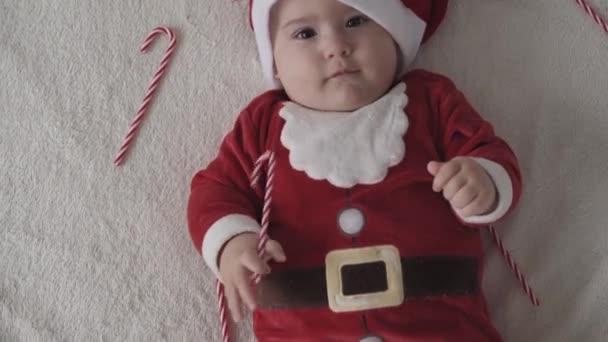 Veselé Vánoce, šťastný nový rok, kojenci, dětství, dovolená koncept - close-up úsměv 7 měsíců legrační novorozenec v Santa Claus klobouk, červená bodysuit hrát na bílé měkké posteli lízat sladké vánoční cukroví