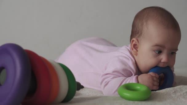 Säugling, Kindheitskonzept - Nahaufnahme von lächelnd glücklich mollig lustig braunäugig pummeliges Gesicht von neugeborenen Kind wach zahnlos 7 Monate Baby Grimassen, schließt Augen liegen auf dem Bett in rosa mit mehrfarbigen Pyramide