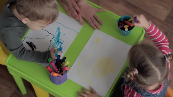 Art, education, childhood, concepts - Little happy smart preschool minor Toddler sibling children draws with felt-tip pens and pencils sit at table indoors. smiling kids brother sister paints indoors