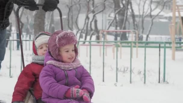 Winter, Childhood, fatherhood, games, family concepts - close up Two happy preschool toddler kids siblings children sledding having fun play together with dad in snowfall cold weather in park outdoors