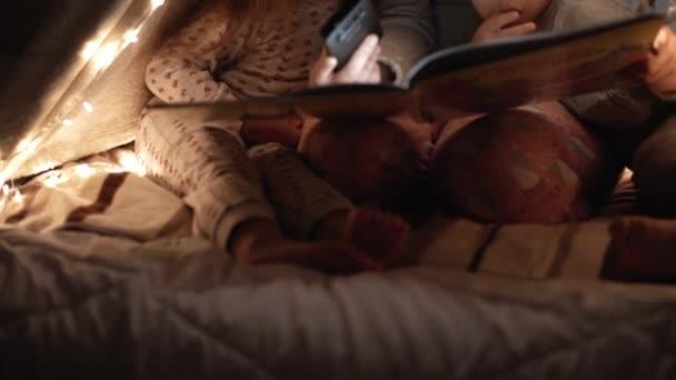 autentické něžné roztomilé maminka a školka děti chlapec a dívka ve stanu doma. mladá žena číst knihu pro děti 2-4 roky ve vigvamu v noci. Rodina, dětství, mateřství, pohodlí a bezpečnost koncepce