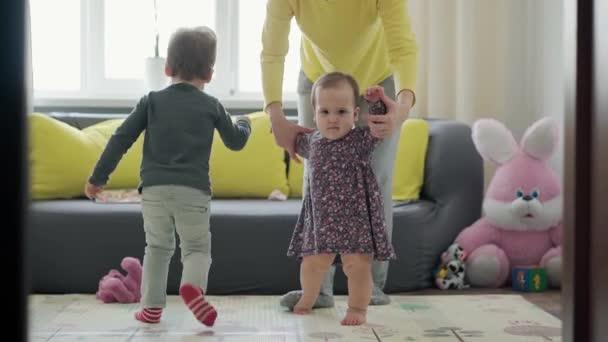 Autentické zblízka mladé neo kavkazské maminka hrát se dvěma malými dětmi dítě holčička a školka chlapec bavit trávit čas doma. mateřství, dětství, rodina, koncepce autenticity