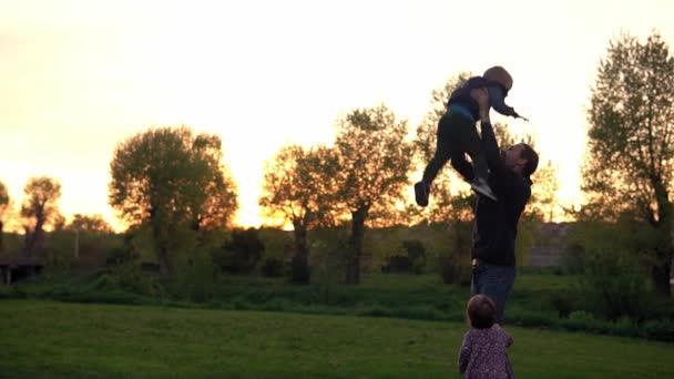 Menschen im Park. glückliche Familiensilhouette bei Sonnenuntergang. Papa wirft Kind in die Luft haben Zeit zu verbringen. Eltern und lustige Kinder, die im Freien spazieren gehen. Vatertag, Kindheit, Elternschaft