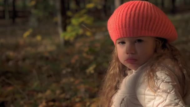 Authentic sad little cute caucasian preschool baby girl 3-4 years in orange beret sitting on plaid in fallen yelow leaves in Autumn park or forest. Children in fall. Nature, Season, Childhood concept.