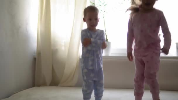 Two smiling preshool, toddler children boy and girl lieing on back in pajamas on white bed. Siblings little twins have fun, happy kids on quarantine at home. Friendship, family, education concept