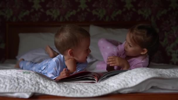 Two cute smiling preshool, toddler children on pajamas read book of fairy tales on bed. Siblings little twins reader have fun. Happy kids on quarantine at home. Friendship, family, education concept