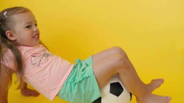 Autentické roztomilé usmívající se školka holčička s klasickou černobílý fotbalový míč pohled na kameru na žlutém pozadí. dítě hraje fotbal v tričku a šortkách. Sport, mistrovství, týmová koncepce