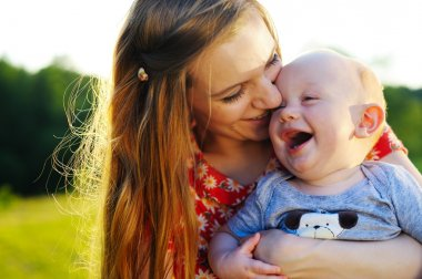 Beautiful Mother And Baby outdoors. Nature. Outdoor Portrait of happy family. Joy.