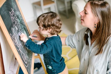 Young mother draws a chalk on a blackboard with his young son. The concept of family