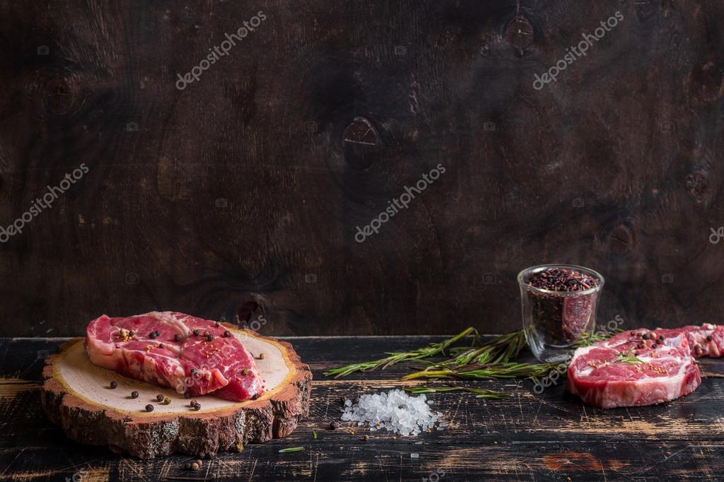 Raw juicy meat steak on dark wooden background ready to roasting