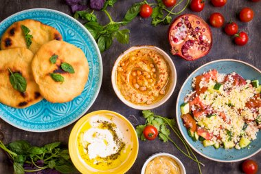 Table served with middle eastern vegetarian dishes. Hummus, tahi
