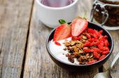 čerstvá snídaně s müsli, jogurt, ořechy, goji bobule a sláma