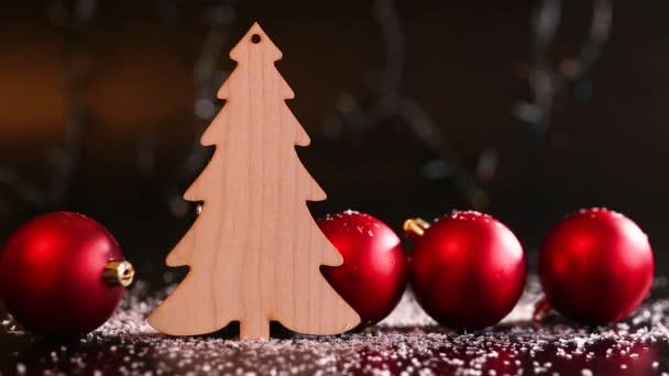 Holzspielzeug in Form einer Tanne auf einem dunklen Tisch mit weißem Schnee und roten Weihnachtskugeln