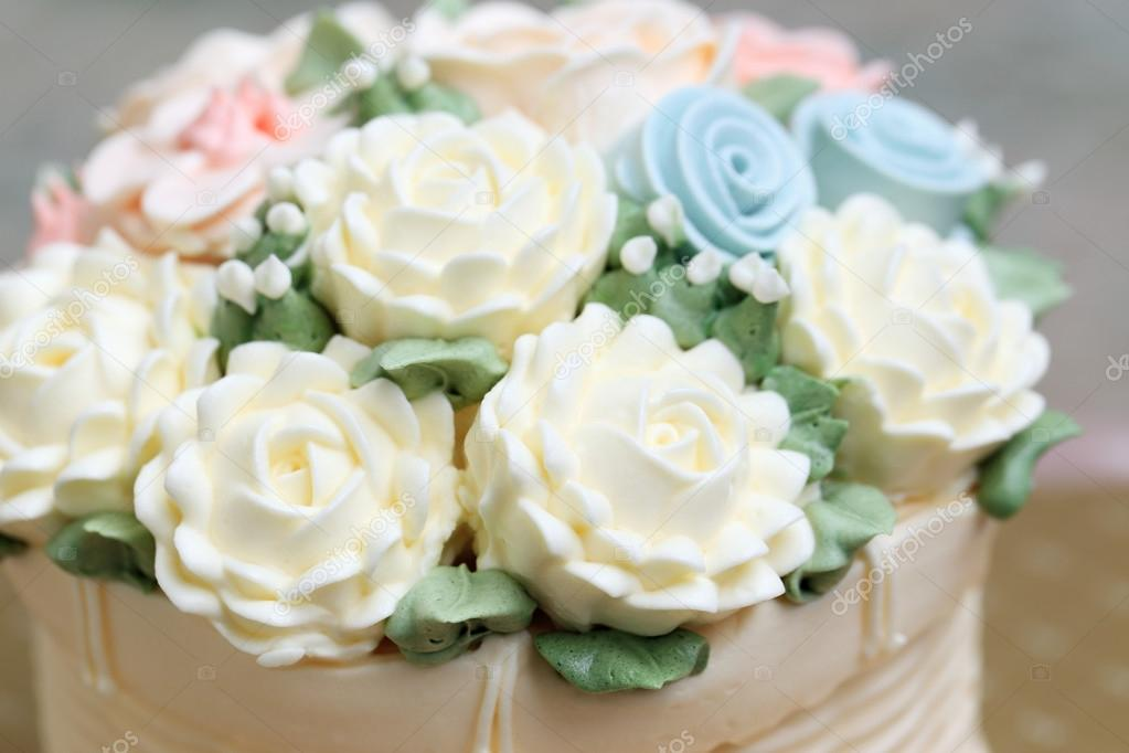 Close up of wedding or birthday cake decorated white flowers made