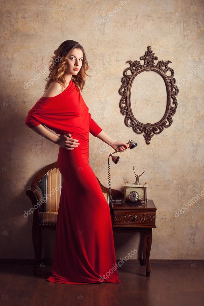 La Chica Del Vestido Rojo Recoge Un Teléfono Retro Foto De