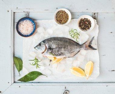 Fresh uncooked sea bream fish with lemon