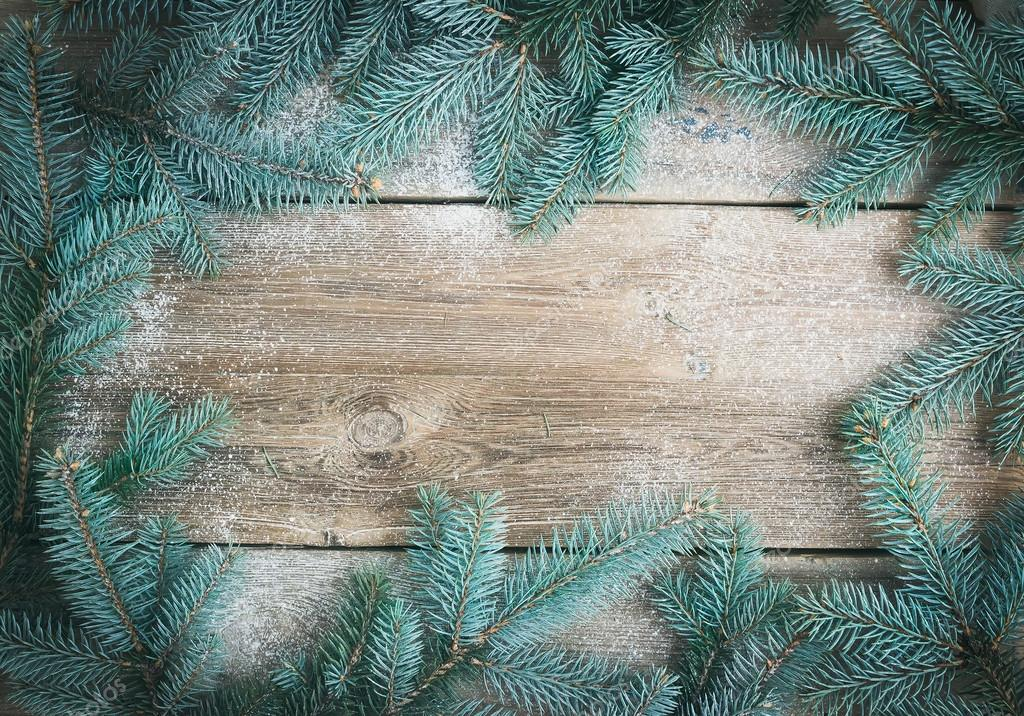 christmas new year theme background a frame of fur tree branches over a rough wooden desk with a copy space in the center photo by sonyakamoz