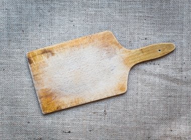 Rustic wooden cutting board over a sackcloth surface