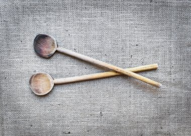 Two rustic wood cooking spoons over a sackcloth surface