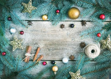 Christmas (New Year) decoration background: fur-tree branches, golden, red and silver glass balls, golden glittering toy stars, cinnamon sticks and anise stars on a rough wooden desk with a copy space stock vector
