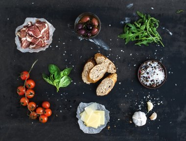 Ingredients for sandwich with smoked meat, baguette, basil, arugula, olives, cherry-tomatoes, parmesan cheese, garlic and spices over black grunge background