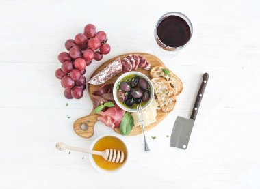 Wine appetizer set. Glass of red, grapes, parmesan cheese, meat variety, bread slices, pecan nuts, honey, olives and basil on rustic wooden board over white backdrop