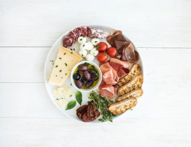 Wine appetizer set. Cherry-tomatoes, parmesan cheese, meat variety, bread slices, dried tomatoes, olives and basil on round ceramic plate over white wood backdrop