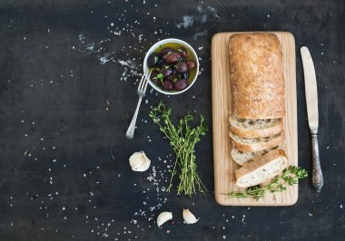 Italian ciabatta bread cut in slices on wooden chopping board with herbs, garlic and olives over dark grunge backdrop, copy space