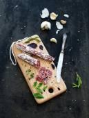 Maso gurmánské občerstvení. Salám, česnek, bagetu a byliny na rustikální dřevěné desce nad grunge tmavé pozadí