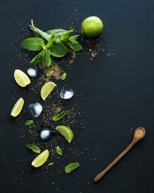 Ingredients for mojito. Fresh mint, limes, ice, sugar over black backdrop. Top view.