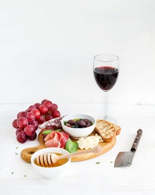 Wine appetizer set. Glass of red, grapes, parmesan cheese, meat variety, bread slices, pecan nuts, honey, olives and basil on rustic wooden board over white backdrop.