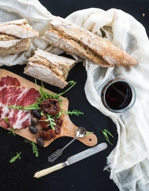 Wine appetizer set: vintage dinnerware, french baguette broken into pieces, dried tomatoes, olives, smoked meat and arugula on rustic wooden board over dark background